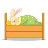 逗人喜爱的微笑的布朗兔宝宝睡眠在床上 免版税库存照片