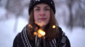 逗人喜爱的微笑的年轻女人画象温暖的夹克的有燃烧的闪烁发光物的在冬天公园 改变从面孔的焦点 股票录像