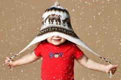 逗人喜爱的微笑的男婴画象被编织的帽子的 库存照片