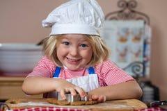 逗人喜爱的微笑的男孩烘烤姜饼 免版税图库摄影