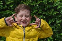 逗人喜爱的微笑的男孩画象在一救生服agai的7岁 库存图片
