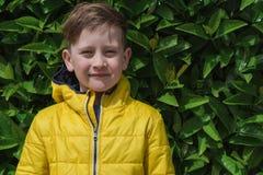 逗人喜爱的微笑的男孩画象在一救生服agai的7岁 免版税图库摄影