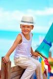 逗人喜爱的微笑的男孩,孩子在长尾巴小船坐热带海滩 免版税库存图片