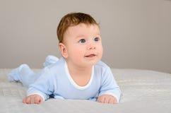 逗人喜爱的微笑的男婴在说谎在他的腹部的床上 免版税库存图片