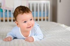 逗人喜爱的微笑的男婴在说谎在他的腹部的床上 免版税库存照片