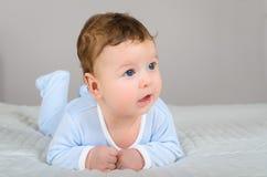 逗人喜爱的微笑的男婴在说谎在他的腹部的床上 免版税图库摄影