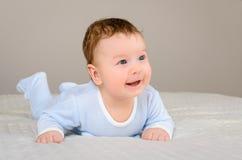 逗人喜爱的微笑的男婴在说谎在他的腹部的床上 图库摄影