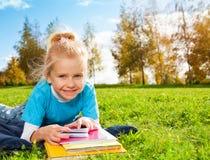 逗人喜爱的微笑的白肤金发的女孩在公园 库存照片