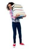 逗人喜爱的快乐的儿童运载的堆书 免版税库存图片