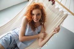 逗人喜爱的快乐的年轻红头发人夫人在吊床说谎 库存图片