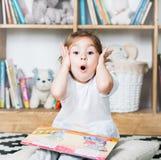 逗人喜爱的情感小女孩阅读书和惊奇 免版税图库摄影