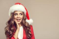 逗人喜爱的惊奇的妇女画象圣诞老人帽子的 图库摄影