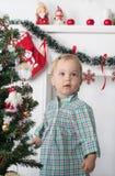 逗人喜爱的惊奇的小女孩在圣诞树附近站立 库存照片