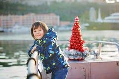 逗人喜爱的愉快的孩子,旅行在湖的一条小船在圣诞节期间 免版税图库摄影