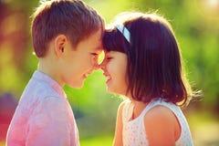 逗人喜爱的愉快的小孩低下他们的头,夏天户外 免版税库存照片