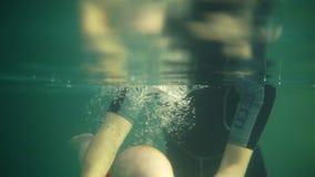 逗人喜爱的愉快的小孩潜水在水下在游泳场并且游泳那里,直到他的母亲帮助他得到 影视素材