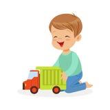 逗人喜爱的愉快的小男孩坐使用与玩具卡车,五颜六色的字符传染媒介例证的地板 向量例证