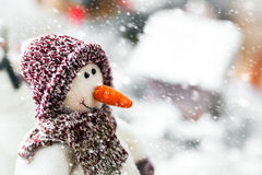 逗人喜爱的愉快的微笑的雪人佩带的冬天围巾和帽子 库存图片
