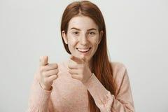 逗人喜爱的愉快的指向与食指的照相机的红头发人白种人妇女特写镜头画象,广泛地微笑和 免版税库存图片