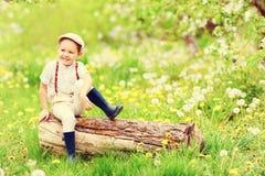 逗人喜爱的愉快的男孩坐木树桩在春天庭院里 免版税库存照片