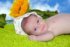 逗人喜爱的愉快的婴孩画象,说谎在绿色地毯 免版税库存照片