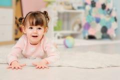 逗人喜爱的愉快的2岁在家使用与玩具的女婴 免版税库存照片