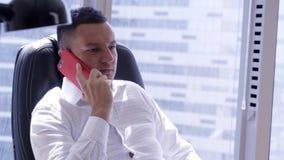 逗人喜爱的成熟深色的人佩带的白色衬衫发表演讲关于红色智能手机 股票视频