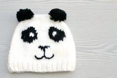逗人喜爱的手工编织的熊猫帽子 免版税库存照片