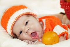 逗人喜爱的打呵欠的新出生的婴孩在一套被编织的橙色服装wi穿戴了 免版税库存图片