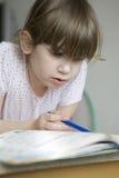 逗人喜爱的执行的女孩家庭作业 图库摄影