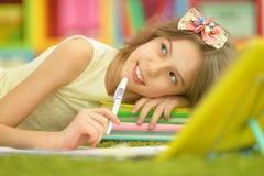 逗人喜爱的执行的女孩家庭作业 库存照片