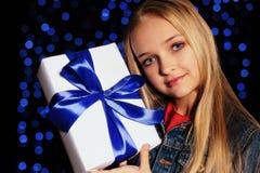 逗人喜爱的拿着礼物箱子的小女孩whith长的金发欢乐照片  免版税库存照片