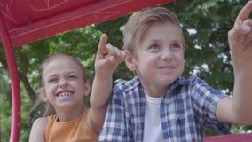 逗人喜爱的指向与手指的男孩和女孩坐摇摆关闭在公园,愉快地笑 两三 股票录像