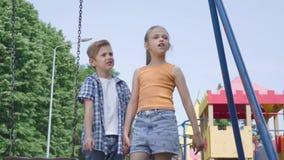 逗人喜爱的指向男孩和的美女有长发的握手在摇摆附近,愉快地微笑户外 A 影视素材