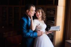 逗人喜爱的接受witn的新娘和新郎预定靠近窗口在老图书馆 免版税图库摄影