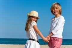 逗人喜爱的握手的男孩和女孩。 免版税库存照片