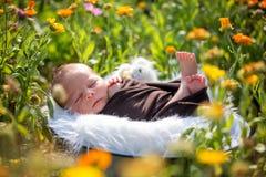 逗人喜爱的新出生的男婴,平安地睡觉在篮子在庭院里 免版税库存照片
