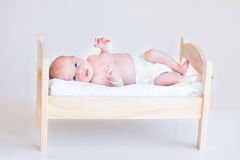 逗人喜爱的新出生的婴孩在玩具床上 免版税库存照片