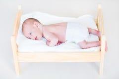 逗人喜爱的新出生的婴孩在玩具床上 免版税图库摄影