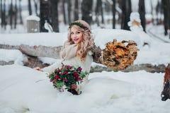 逗人喜爱的新娘坐雪近对木日志并且拿着花束 户外婚姻冬天的新娘新郎 免版税库存图片