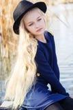 逗人喜爱的时尚小女孩在湖附近休息 免版税库存照片