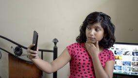 逗人喜爱的时髦的印度亚裔采取selfie的白种人愉快的女孩孩子做噘嘴在手机正面图画象 影视素材