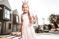 逗人喜爱的时髦的黑眼睛的滑稽女孩佩带的白色礼服的感觉 免版税库存图片