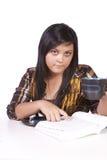逗人喜爱的服务台她学习的妇女 免版税库存照片