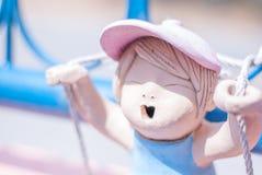 逗人喜爱的桃红色陶瓷女孩玩偶演奏在蓝色的绳索摇摆我 免版税库存照片