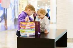 逗人喜爱的检查在购物中心的小男孩和女孩购物袋 库存图片