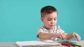 逗人喜爱的欧洲男孩画坐在与色的铅笔的桌上在册页 股票视频