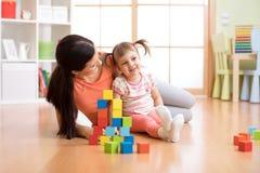 逗人喜爱的母亲和儿童女孩一起使用与立方体 免版税库存照片