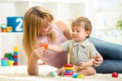 逗人喜爱的母亲和儿童男孩一起演奏室内在 免版税库存照片
