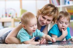 逗人喜爱的母亲和她的一起读两个儿子的孩子 库存图片